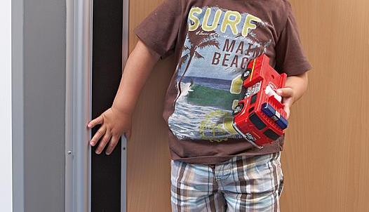 Example of child's fingers and an automatic swing door protected with the Hotron FP200 Finger Guard