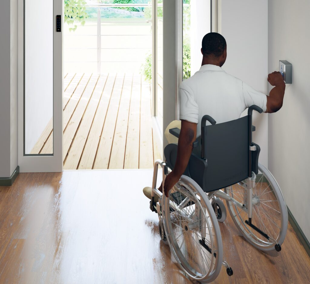 Wheelchair user using automatic swing door and Hotron's Stainless Steel Back-lit Push Pad