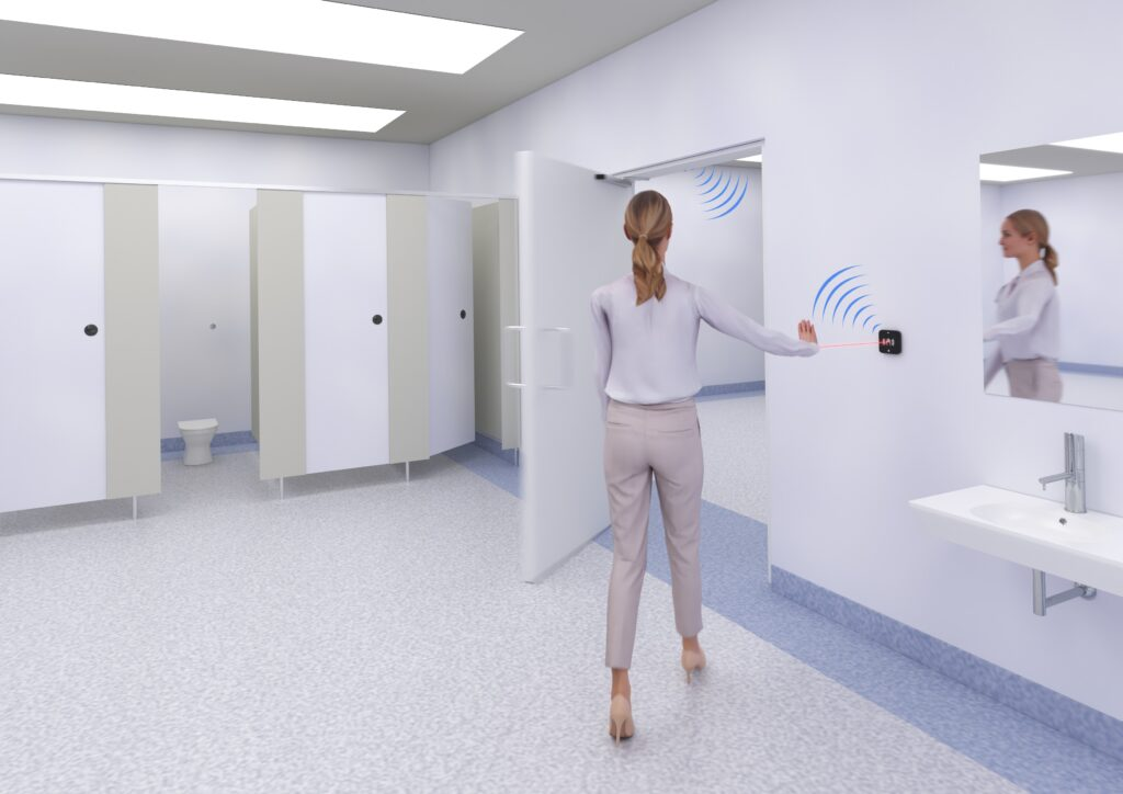 Pedestrian in public toilet using Hotron AerWave hygienic, touchless and wireless automatic door activation switch.
